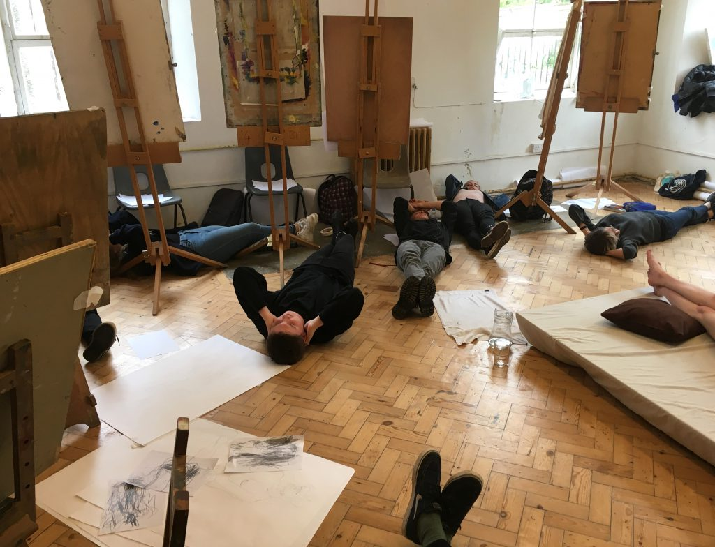 Students lying on the floor during a life drawing study
