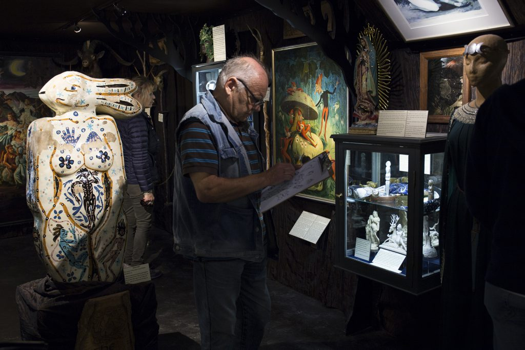 A man drawing in front of a museum display case