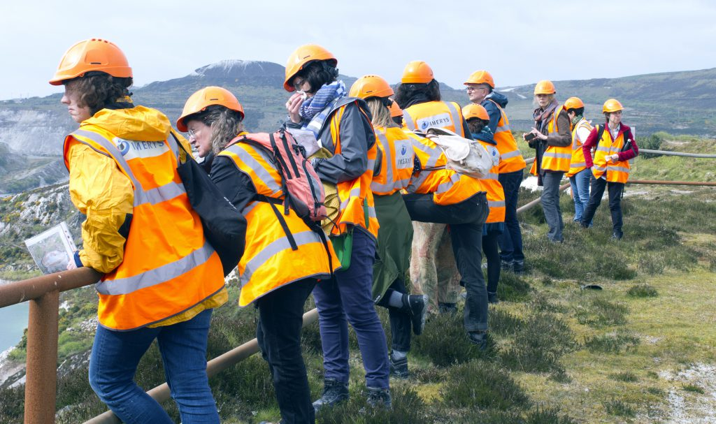 A group of people looking over a fence, dressed in hard hats and high vis jackets