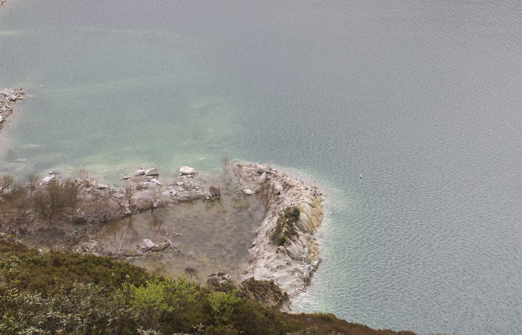 A rock formation on the edge of a body of water
