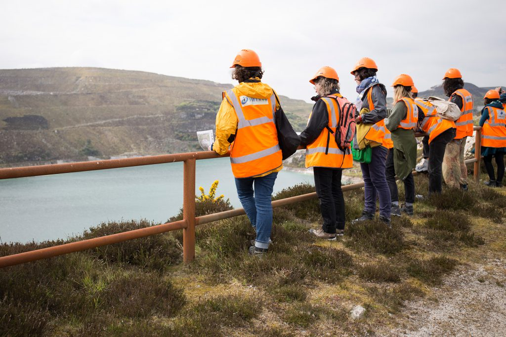 People dressed in high visibility jackets looking into a china clay pit