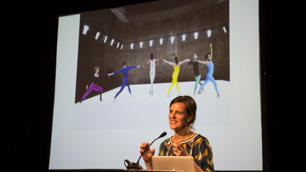 Curator speaking at a lecturn in front of a projection screen