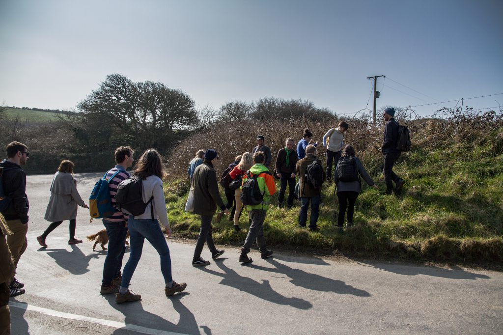 People crossing a lane and walking into a field