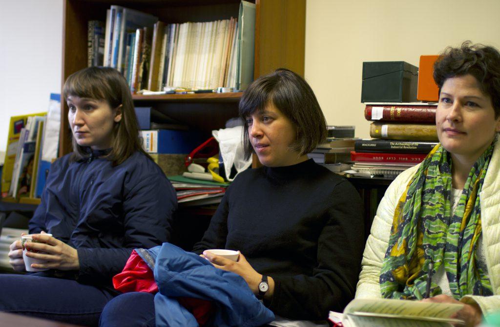 Three women seated on a sofa listening