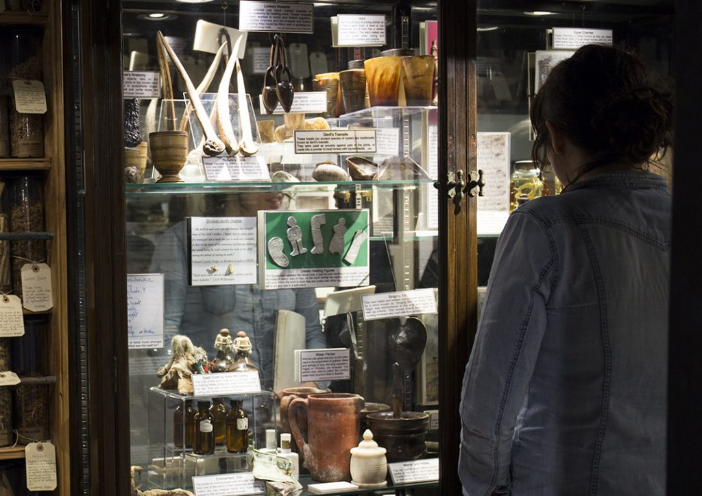 A woman looking at artefacts in a museum display case