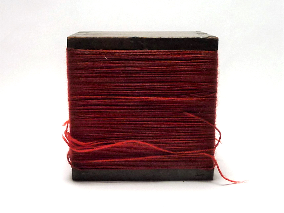 A wooden box, bound in red twine