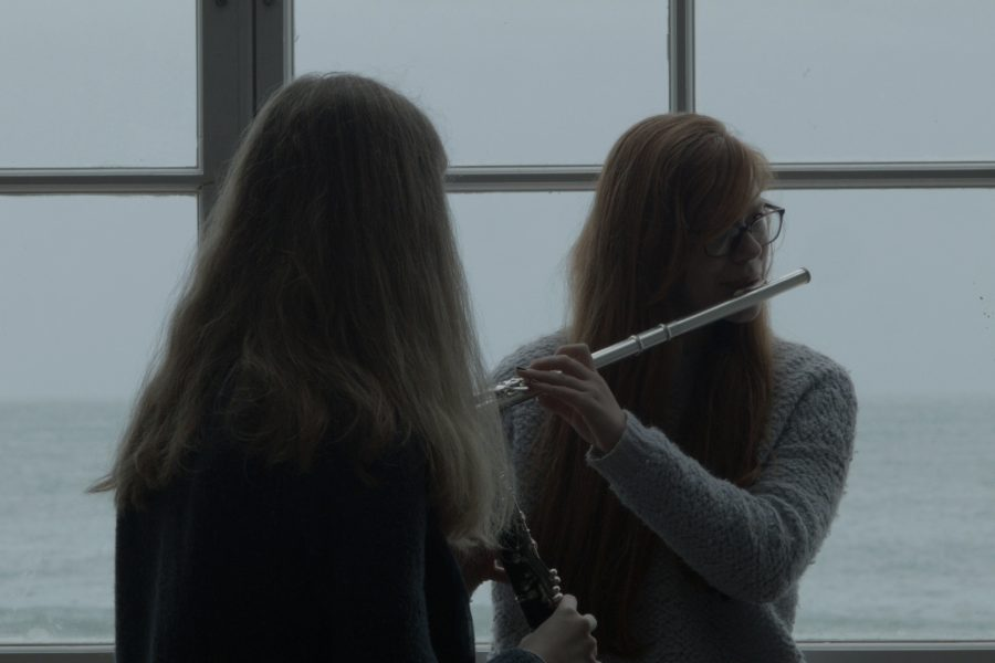 A film still showing two young women in front of a window, playing a flute and a clarinet